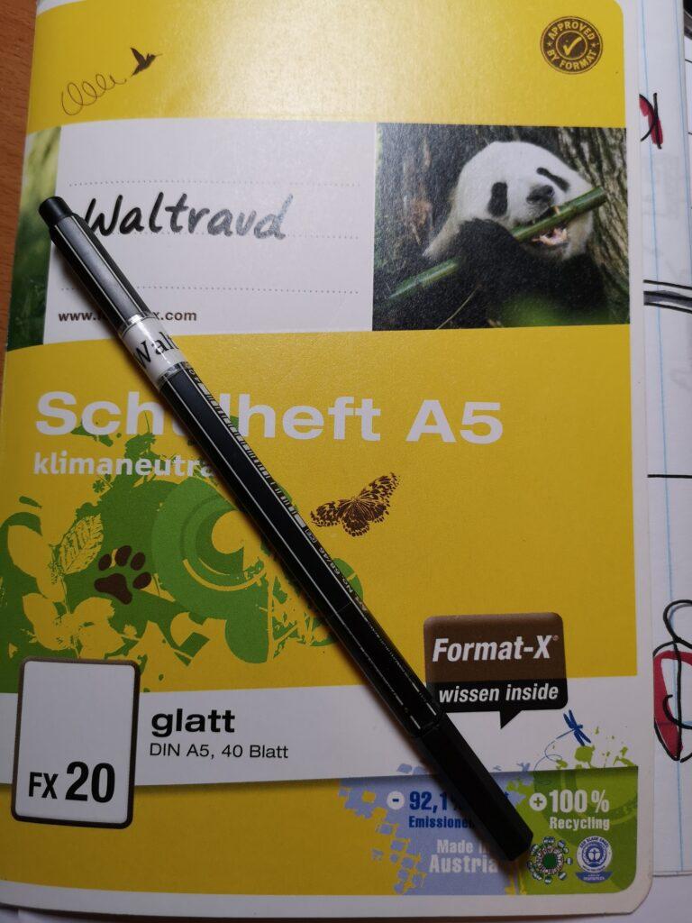 Das ist ein Schulheft, ein kleines Schulheft. Es hat keine Linien. Und man sieht einen schwarzen Stift. Der Stift ist von der Firma Stabilo. Auf dem Stift und auf dem Heft steht der Name Waltraud. Stift und Hefte waren ein Geschenk.
