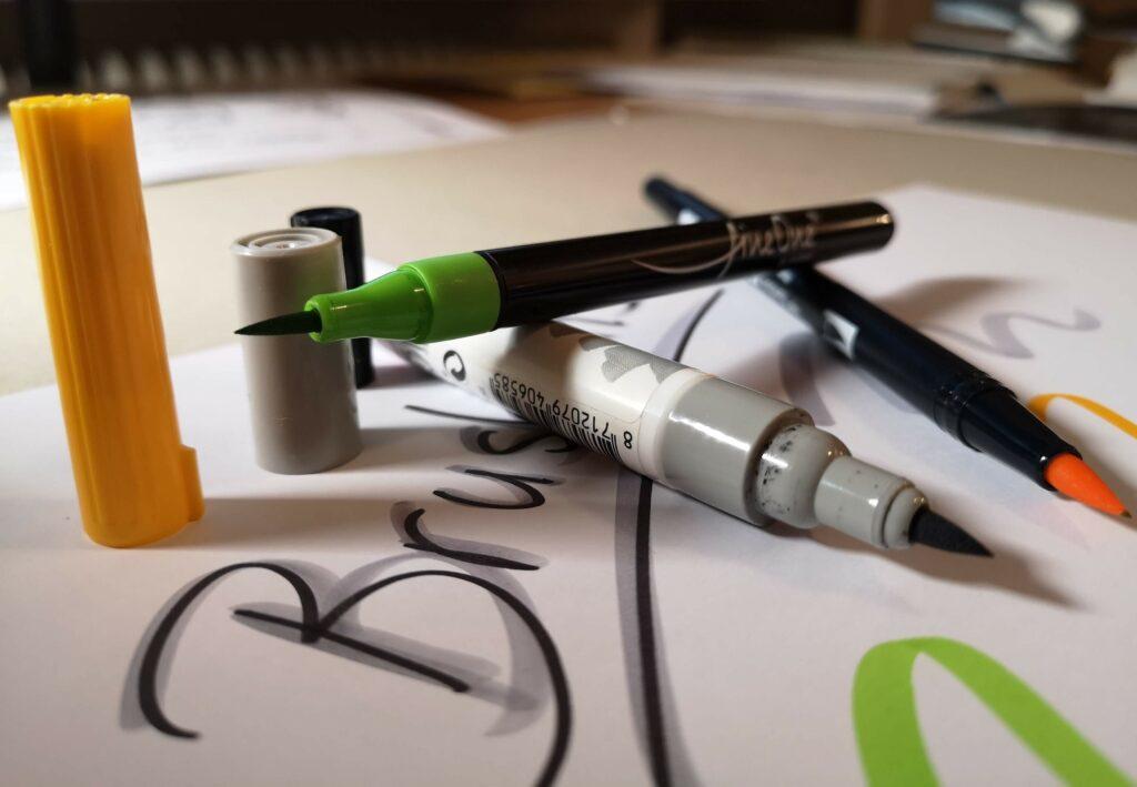 Auf dem Bild sieht man Brushpens oder Pinselstifte in Grün, Grau und Gelb. Diese Stifte sind zum Setzen von Akzenten ideal. Deshalb sollte das Papier sehr glatt sein, damit die Pinselstifte nicht ausfransen.