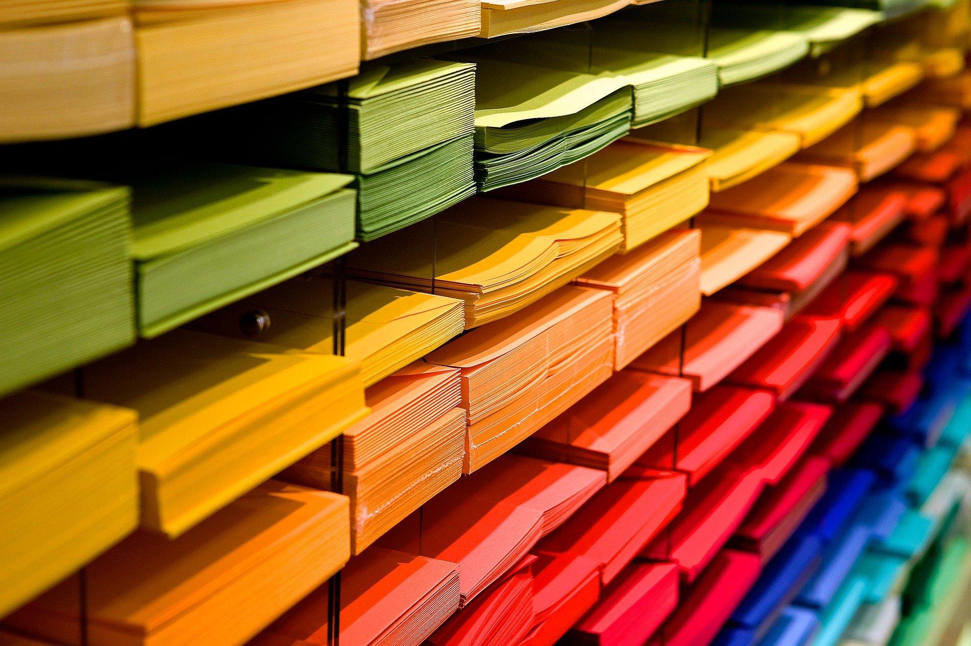 Auf dem Bild sieht man buntes Papier, das nach den Farben Grün, Gelb, Orange, Rot geordnet ist.