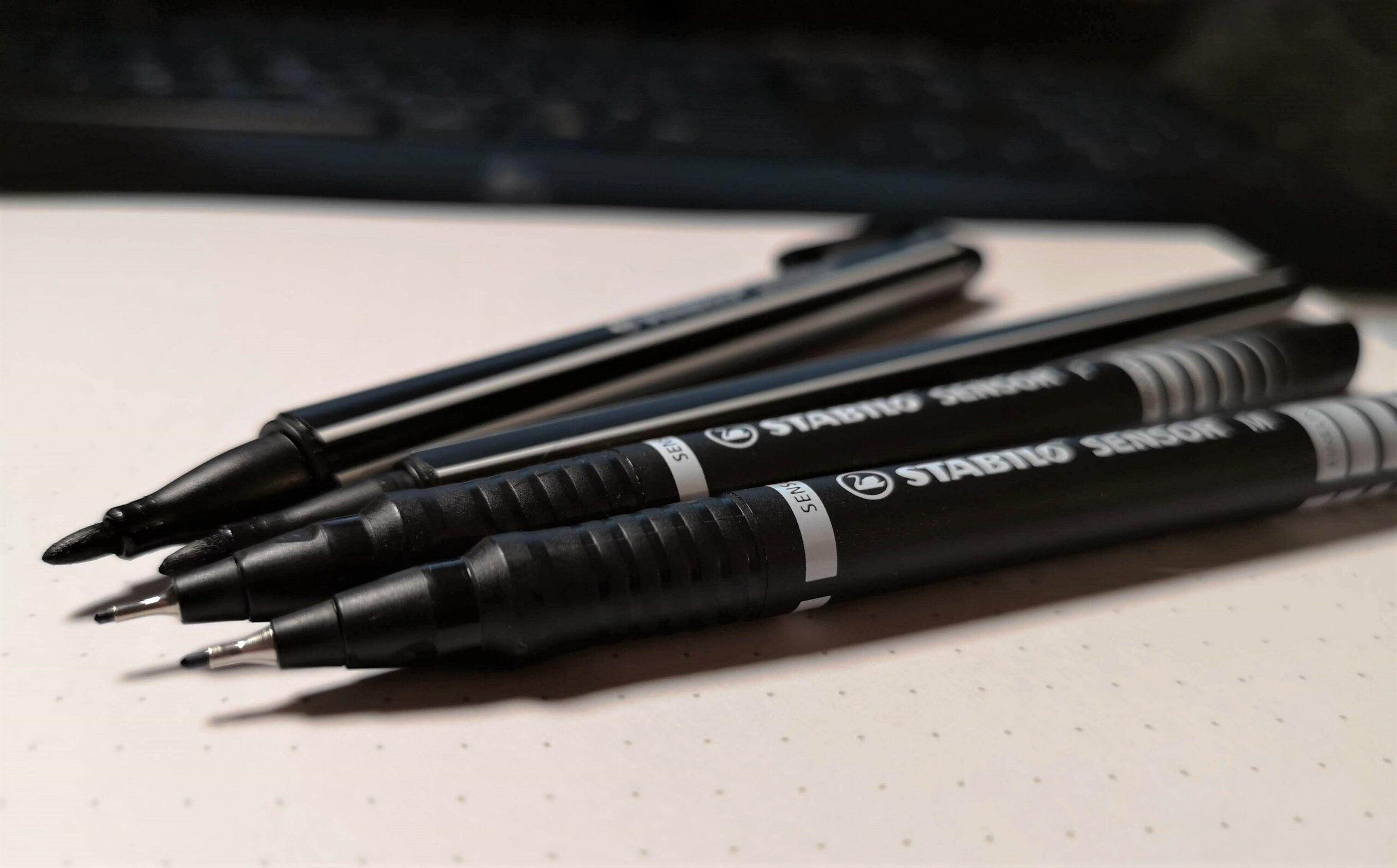 Auf dem Bild sieht man vier schwarze Stifte, die sehr gut zum Zeichnen und Sketchnoten geeignet sind. Sketchnotes mit diesen Stiften sehen immer gut aus.